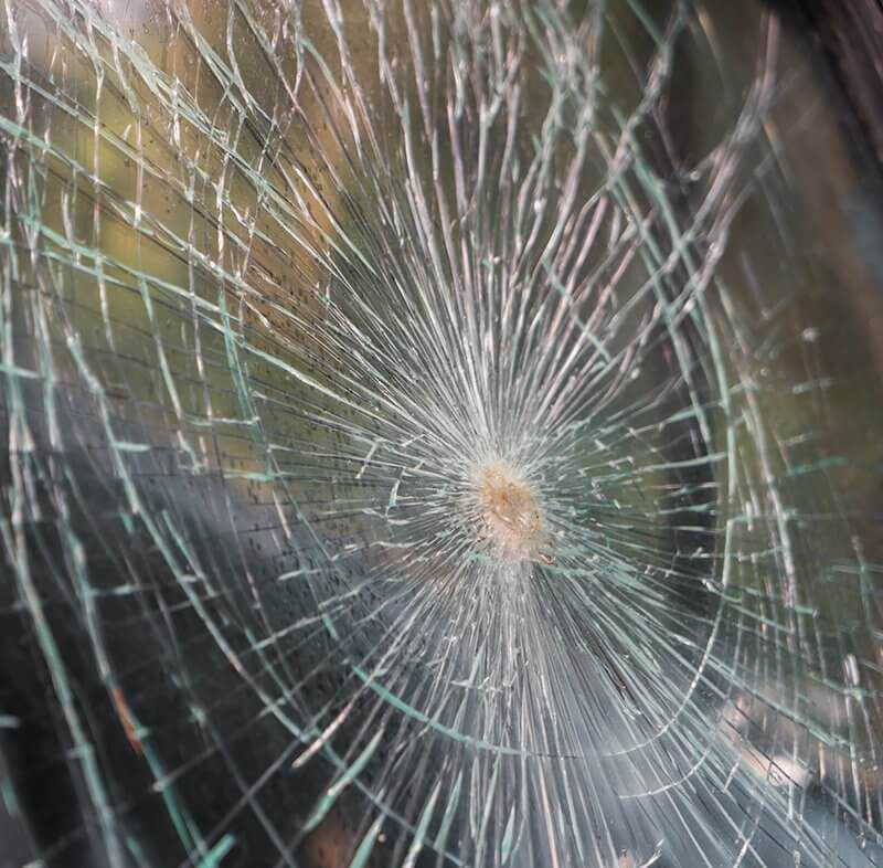 Glass broken cracks splinters in front of car Filtered image